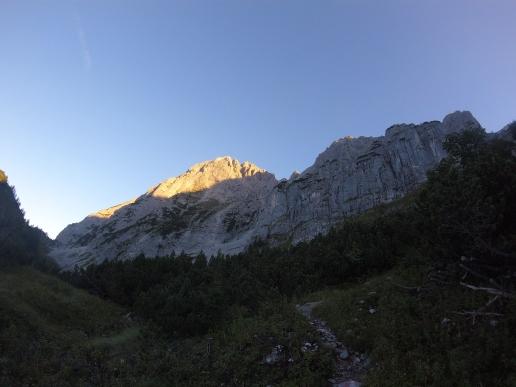 Die ersten Sonnenstrahlen streichen über die Berggipfel